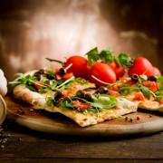 Pizza aus dem Steinofen mit Tomaten und Rucola